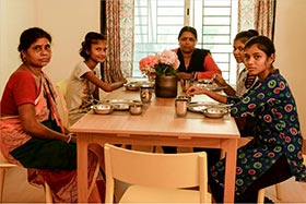 Female cancer patients interacting over a meal at Karo Home in Mumbai